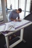 Сфокусированное планирование дизайнера по интерьеру на бумаге в творческом офисе Стоковое фото RF