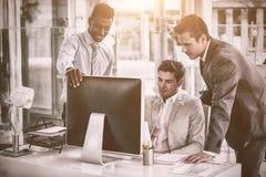 Сфокусированные бизнесмены смотря в компьютер Стоковое фото RF