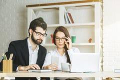 Сфокусированные бизнесмен и женщина используя smartphone стоковое изображение