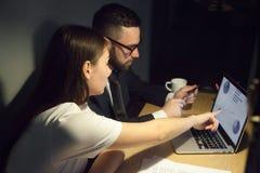 Сфокусированные коллеги анализируя компанию приносят пользу работать поздно внутри  Стоковые Изображения