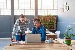 Сфокусированные молодые бизнесмены используя компьтер-книжку на столе офиса Стоковое Изображение RF