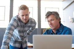 Сфокусированные молодые бизнесмены используя компьтер-книжку на столе офиса Стоковые Изображения