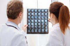 Сфокусированные доктора держа MRI просматривают против света стоковое фото