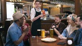 Сфокусированные пив и коктейли молодой официантки служа к группе в составе молодые студенты, друзья видеоматериал