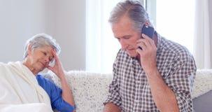 Сфокусированные пожилые пары вызывая доктора сток-видео