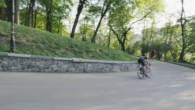 Сфокусированные sportive езды triathlete вниз с холма на curvy поворачивать дороги r ( акции видеоматериалы