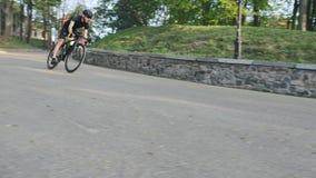 Сфокусированные sportive езды triathlete вниз с холма на curvy поворачивать дороги r видеоматериал