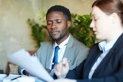 Сфокусированный африканский бизнесмен обсуждая документы с коллегой Стоковое Изображение RF
