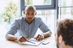 Сфокусированный Афро-американский бизнесмен слушая к коллеге на деловой встрече Стоковое Фото