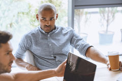 Сфокусированный Афро-американский бизнесмен слушая к коллеге на деловой встрече Стоковые Изображения RF