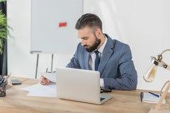 Сфокусированный бизнесмен делая обработку документов на рабочем месте в офисе Стоковая Фотография RF