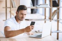 Сфокусированный бизнесмен используя smartphone на рабочем месте с компьтер-книжкой в офисе Стоковые Фото