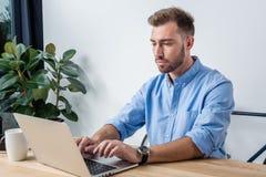 Сфокусированный бизнесмен печатая на компьтер-книжке пока работающ в офисе Стоковое Фото