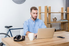 Сфокусированный бизнесмен печатая на компьтер-книжке пока работающ с компьтер-книжкой в офисе Стоковое фото RF