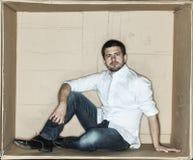Сфокусированный бизнесмен сидя в коробке стоковое фото rf