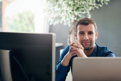 Сфокусированный бизнесмен сидя на компьютере в офисе Стоковое Фото