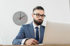 Сфокусированный бизнесмен смотря экран компьтер-книжки на рабочем месте в офисе Стоковые Фото