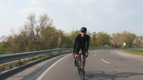 Сфокусированный велосипедист на катании велосипеда дороги к камере на заходе солнца Велосипедист нося черный jersey и шорты r Мед видеоматериал