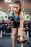 Сфокусированный вес гантели женщины поднимаясь в руке Стоковое Изображение