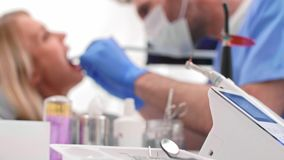 Сфокусированный дантист с зубоврачебным сверлом очищая зубы плохого пациента акции видеоматериалы