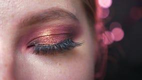 Сфокусированный изумительный голубой глаз в грести розовые тени для век смотря холодок камеры, чистую красоту модели на черной пр видеоматериал