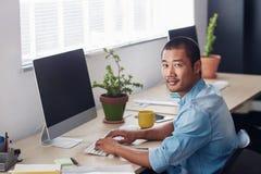 Сфокусированный молодой азиатский дизайнер на работе на компьютере офиса Стоковое Изображение