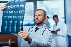 Сфокусированный доктор анализируя изображение рентгеновского снимка с коллегами позади Стоковая Фотография