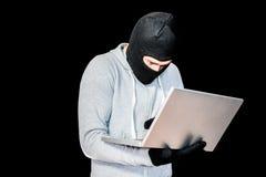 Сфокусированный похититель с клобуком печатая на компьтер-книжке Стоковое Изображение RF