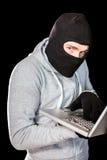 Сфокусированный похититель с клобуком печатая на компьтер-книжке Стоковые Фотографии RF