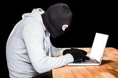 Сфокусированный похититель с клобуком печатая на компьтер-книжке Стоковое Изображение