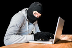 Сфокусированный похититель с клобуком печатая на компьтер-книжке Стоковые Изображения
