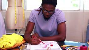 Сфокусированный студент моды рисуя платье видеоматериал