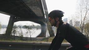 Сфокусированный уверенный велосипедист на велосипеде Солнце светит до конца Река и мост в предпосылке Близкий поднимающий вверх в акции видеоматериалы