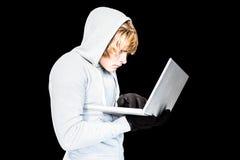 Сфокусированный человек с hoodie печатая на компьтер-книжке Стоковые Изображения