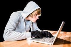 Сфокусированный человек с hoodie печатая на компьтер-книжке Стоковые Фото