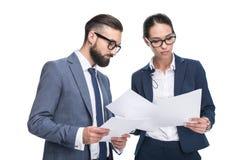 2 сфокусированных предпринимателя в костюмах смотря бумаги, Стоковое Изображение