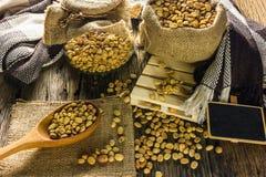 Сфокусируйте кофейные зерна пятна и кофейную чашку на деревянном столе Стоковые Изображения RF