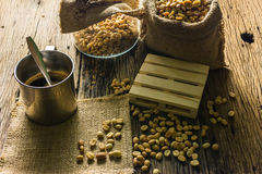 Сфокусируйте кофейные зерна пятна и кофейную чашку на деревянном столе Стоковые Фото