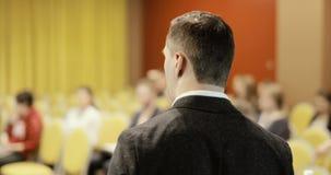 Сфокусируйте на бизнесмене адресуя конференцию для того чтобы делегировать raiseing ее рука для того чтобы спросить вопрос сток-видео