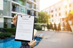 Сфокусируйте на документе держа девушку на предпосылке нового здания солнечного света Фронт используемый с открытой лицензией шри стоковое фото