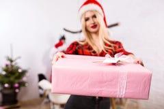 Сфокусируйте на giftbox в руках женщины на переднем плане Красивая блондинка в шляпе Санты, красной рубашке в клетке и черноте Стоковые Фото
