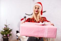 Сфокусируйте на giftbox в руках женщины на переднем плане Красивая блондинка в шляпе Санты, красной рубашке в клетке и черноте Стоковое Изображение