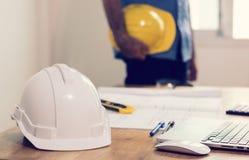 сфокусируйте на safty шлеме на положении работая стола и 2 инженеров Стоковые Изображения