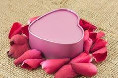 Сформированная сердцем коробка металла с красной розой помещена на дерюге Стоковые Изображения