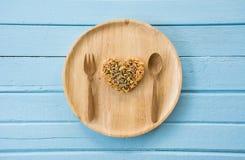 Сформируйте сердце сделанное от всего зерна на деревянном блюде стоковые изображения