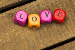 Сформулируйте влюбленность на пестротканых деревянных кубиках на древесине Стоковое Изображение