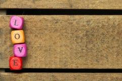 Сформулируйте влюбленность на пестротканых деревянных кубиках на древесине Стоковые Изображения