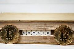 Сформулируйте вознаграждение написанное в деревянных блоках в книге и bitcoin стоковые фотографии rf