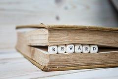 Сформулируйте вознаграждение написанное в деревянных блоках в книге стоковое фото