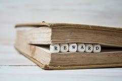 Сформулируйте вознаграждение написанное в деревянных блоках в книге стоковое изображение